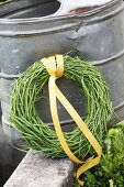 Wreath of rapeseed pods tied with yellow ribbon