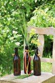 Ox-eye daisies, ears of barley and rapeseed flowers in swing-top bottles