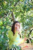Mädchen isst einen Apfel bei der Apfelernte