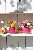 Posies of zinnias in glasses of water wrapped in felt ribbons and apples on white shelf