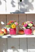 Zinniensträusschen in Wassergläsern mit Filzband und Äpfel in weissem Regal
