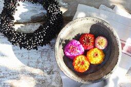 Kränzchen aus Hartriegelbeeren und Zinnienblüten in einer Schale mit Wasser