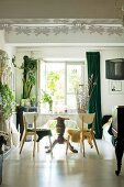 Table with pedestal leg and house plants in dining room with white floor