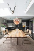 Modern dining table and cantilever chairs in front of open-plan kitchen