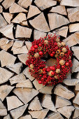 Wreath of red berries, walnuts and medlars on stacked firewood