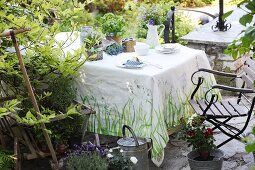 Painted tablecloth and jug vase on table on garden terrace
