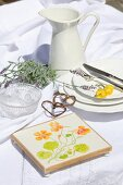 Coaster painted with floral motif on white tablecloth