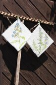 Hand-made pot holders with painted and embroidered floral motifs run from wooden rake