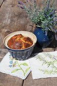 Hand-made pot holders and cake and lavender in ceramic vessels on wooden table