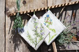 Hand-made potholders with floral motifs and bunch of lavender hung from wooden rake leant against rustic board wall