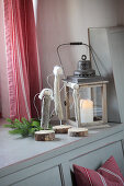 Hand-crafted driftwood angels and candle lantern on windowsill