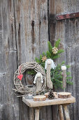 Angels hand-made from driftwood on wooden stool against wooden door