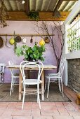 Table and chairs on Mediterranean terrace with lilac back wall
