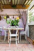 Tisch und Stühle auf mediterraner Terrasse mit lilafarbener Wand