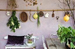 Deko hängt an lilafarbener Wand auf mediterraner Loggia