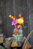 Dahlias, physalis and rose hips in glass bottles