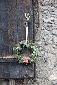 Wreath of ivy with pink flowers hung from rustic shutter