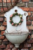 Romantic wreath of ivy leaves and roses hung on old sink