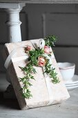 Romantically wrapped gift decorated with roses and ivy tendrils