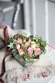 Romantic arrangement of ivy and roses in heart-shaped vintage container
