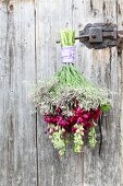 Bouquet of stocks and sea lavender hung from door