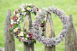 Two flower wreaths hung from rustic garden fence