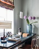 Table lamp, vase of flowers and books on masculine desk
