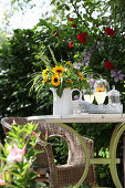 Sunflowers and ornamental grasses in jug on garden table with wicker armchair in background