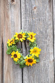 Wreath of sunflowers on wooden surface