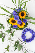 Sunflowers, cornflowers, blades of grass and clematis tendrils in wire basket next to wreath of cornflowers
