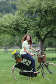 Young woman on bicycle with basket full of sunflowers