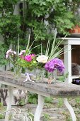 Various flowers in glasses of water on wooden bench