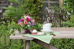 Wildly romantic bouquet on garden table set for afternoon coffee