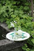 White flowers in small glass vases on retro tray
