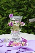 Romantic candle lantern decorated with purple hydrangea and phlox flowers