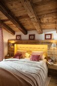 Double bed with yellow button-tufted headboard surrounded by rustic wooden panelling