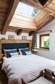 Double bed with rustic headboard in attic bedroom