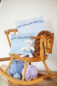 Arrangement of vintage rocking horse, hand-made cushion covers and soft toy