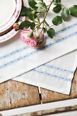 Roses on hand-made place mats with pale blue floral trim
