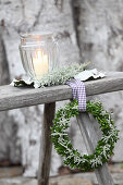 Wreath of box and santolina with ribbon on wooden bench