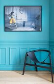 Black designer chair against turquoise wall