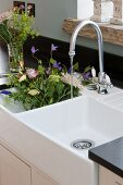 Bouquet of flowers in white, double Belfast sink with vintage-style tap fitting