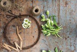 Kranz aus rostigem Draht, Blumen und Paketschnur auf abgenutzem Tisch
