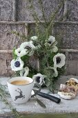 Cup with stag motif and sliced stollen in front of wreath of anemones