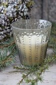 Vintage-style patterned glass candle lantern amongst larch twigs