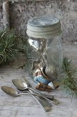 Iced biscuit shaped like boy on sledge leaning against screw-top jar holding silver cutlery