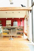 Island counter, bar stools and red wall in open-plan kitchen