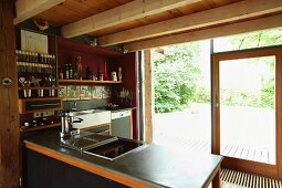 Wood-beamed ceiling in open-plan kitchen with view of garden