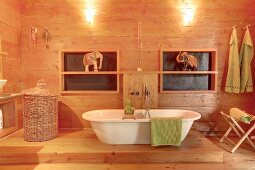 White, free-standing bathtub and elephant ornament in wood-panelled bathroom
