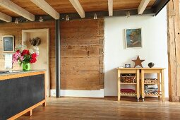 Steel beam and pillar against solid wooden wall in open-plan living area